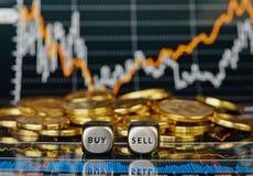 Corta cubos com as palavras VENDEM A COMPRA e as moedas douradas. Imagens de Stock Royalty Free