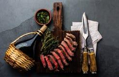 Corta el filete de carne de vaca del hecho con la salsa de la hierba, botella de vino, cubiertos del vintage Fotos de archivo