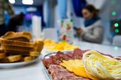 Corta el queso y la carne en la placa en la tabla de cena fotos de archivo libres de regalías