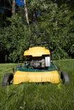 Cortacéspedes que corta la hierba larga en un patio trasero Imagen de archivo libre de regalías