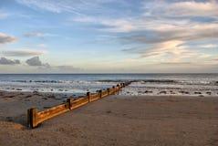 Cortacircuítos de onda de Wodden en el cielo dramático del ingenio de la playa Foto de archivo