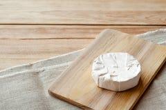 Cortado em volta do queijo do camembert em uma placa de madeira Fotografia de Stock