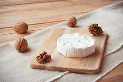 Cortado em volta do queijo do camembert em uma placa de madeira com porcas Imagens de Stock Royalty Free