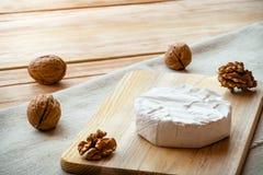Cortado em volta do queijo do camembert em uma placa de madeira com porcas Fotos de Stock Royalty Free