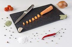 Cortado en pequeños pedazos la zanahoria en una tabla de cortar oscura imagen de archivo