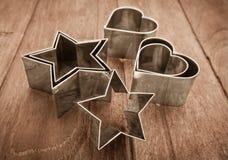 Cortador asteroide y en forma de corazón de los pasteles en la tabla de madera Fotografía de archivo libre de regalías
