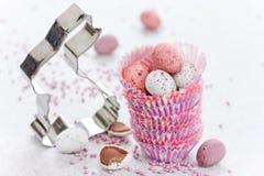 Cortador da cookie do coelhinho da Páscoa e ovos dos doces de chocolate mini no pape Fotografia de Stock