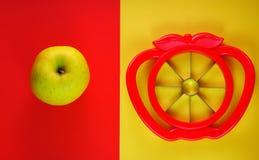Cortador de Apple con una manzana en fondo rojo y amarillo foto de archivo