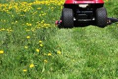Cortador de grama do trator que corta a grama na primavera Foto de Stock Royalty Free