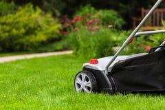 Cortador de grama em um gramado imagens de stock