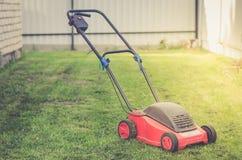 Cortador de grama em um gramado verde/gramado de sega na grama na jarda da casa de campo fotografia de stock