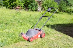 Cortador de grama que corta a grama verde no quintal Fundo de jardinagem Imagens de Stock