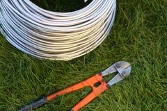 Cortador de perno cerca del alambre de la bobina en la hierba Herramienta, tecnología imagenes de archivo