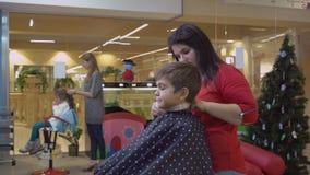 Cortador del pelo con el niño en los peluqueros almacen de video