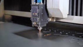 Cortador industrial do laser com faíscas A cabeça programada do robô corta com o auxílio de uma folha enorme da temperatura do me filme