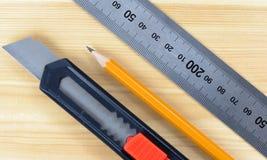 Cortador, lápiz de madera y regla en la tabla de madera Fotografía de archivo libre de regalías