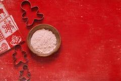 Cortadores da cookie da composição do Natal e uma bacia de farinha no fundo vermelho fotografia de stock royalty free
