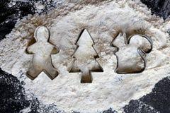 Cortadores da cookie do Natal na farinha e no fundo preto imagem de stock royalty free