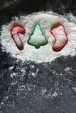 Cortadores da cookie do Natal no fundo da farinha do cozimento fotos de stock royalty free