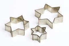 Cortadores dados forma de três estrelas da cookie do Natal sobre o branco Imagem de Stock