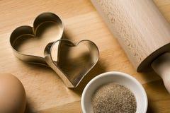 Cortadores de la galleta e ingredientes en forma de corazón de la hornada Fotos de archivo libres de regalías