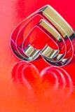Cortadores de la galleta en fondo rojo fotografía de archivo