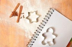 Cortadores de los pasteles del pan de jengibre en tabla de cortar de madera Li de la Navidad Foto de archivo libre de regalías