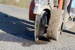 Cortadores del asfalto en el sitio de trabajo Fotografía de archivo