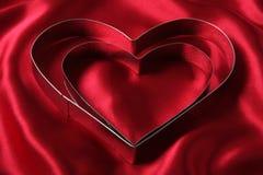 Cortadores en forma de corazón de la galleta en el satén rojo foto de archivo