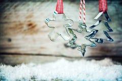 Cortadores rústicos de la galleta de Navidad con nieve del invierno Imagen de archivo libre de regalías