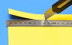 Cortan un pedazo de papel amarillo con un cuchillo y una regla del acero inoxidable Foto de archivo libre de regalías
