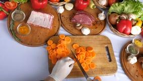 Cortando cenouras em uma placa de corte, cozinhando um prato, salada, preparando-se para cozinhar A cozinha do restaurante carne  video estoque