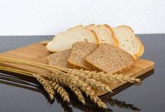 Cortando dois tipos de pão com as orelhas do trigo na placa de madeira Fotografia de Stock Royalty Free