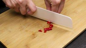 Cortando e cortando a pimenta de pimentão encarnado como parte da receita do cozimento de casa vídeos de arquivo