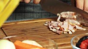 Cortando el tocino para cocinar el desayuno de la quiche almacen de metraje de vídeo