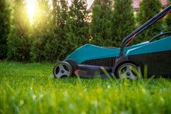 Cortando a grama com cortador de grama bonde Fotos de Stock