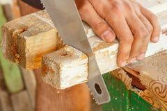 Cortando a los tableros de madera en una mano vio Fotos de archivo libres de regalías