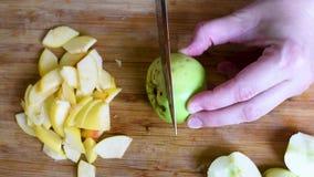 Cortando maçãs em fatias e em metades em uma placa de corte com uma faca filme