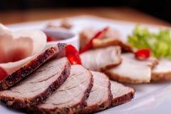 Cortando o bacon, a salsicha, o prosciutto e a carne curada em uma tabela comemorativo imagens de stock