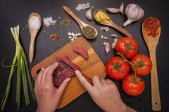 Cortando o bife cru para cozinhar Imagens de Stock Royalty Free