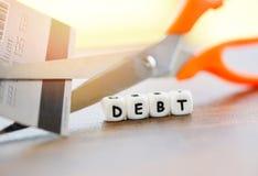 Cortando o cartão do débito/crédito do corte com as tesouras para que a parada pague o dinheiro para proteger a crise financeira  imagem de stock