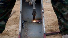 Cortando o ferro com a tocha do gás no trabalho no canteiro de obras filme