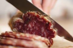 Cortando o fim italiano do salame acima do tiro imagem de stock royalty free
