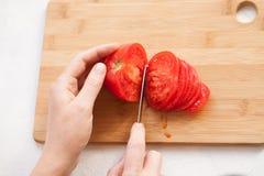 Cortando o meio tomate em fatias na cozinha embarque imagem de stock