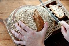 Cortando o pão ácido da massa Imagens de Stock