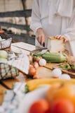 Cortando o queijo e a tabela de madeira dos vegetais imagem de stock royalty free