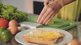 Cortando o queijo macio para o sanduíche em uma mesa de cozinha, mãos da mulher filme