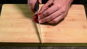 Cortando o tomate de cereja com a faca na placa de madeira filme