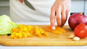 Cortando a pimenta doce na placa de corte de madeira video estoque