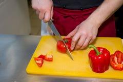 Cortando a pimenta doce na placa de corte de madeira m?os masculinas cortadas com pimenta de sino vermelha da faca grande Close-u imagens de stock royalty free